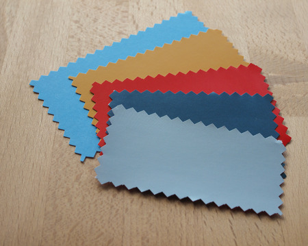 zig: Blue red yellow paper swatch with zig zag border cut with pinking shears