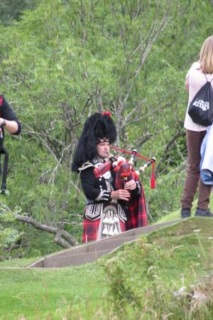 sporran: URQUHART CASTLE, SCOTLAND, UK - CIRCA AUGUST 2015: Scottish bagpiper dressed in traditional red and black tartan dress