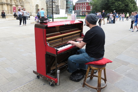 fortepian: YORK, UK - CIRCA AUGUST 2015: Karl Mullen street piano player performing as usual on the street of York