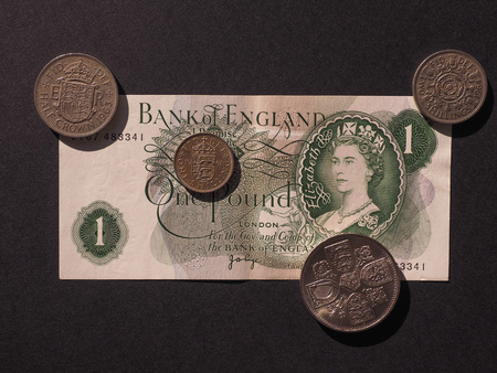 70's: Pound banknote from the 70s and coins currency of the United Kingdom now withdrawn