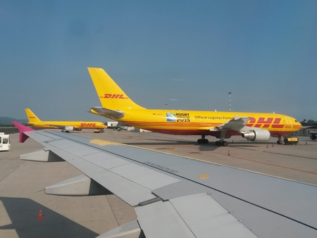 mailing: ORIO AL SERIO, BERGAMO, ITALY - CIRCA JULY 2014: DHL mailing company aircrafst parked at the airport with passenger shuttle