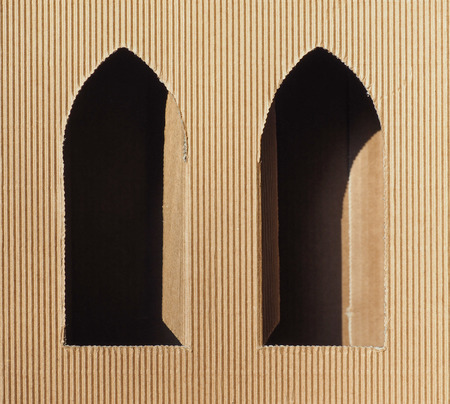 gothic window: Brown corrugated cardboard with gothic window openings useful as a background Stock Photo
