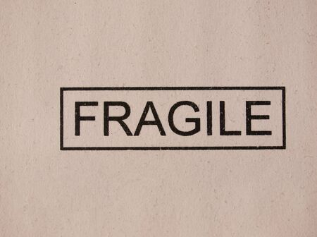 stamped: Fragile stamped on a grey corrugated cardboard Stock Photo