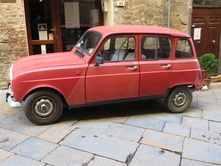 volterra: VOLTERRA, ITALY - CIRCA DECEMBER 2014: A red Renault 4 parked in the old city centre Editorial