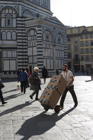 porter: FLORENCE, ITALY - CIRCA JANUARY 2016: unidentified porter carrying two heavy cardboard box on a carrier on Cathedral square