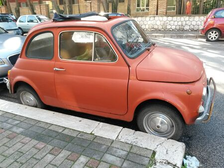 means of transportation: ROME, ITALY - CIRCA OCTOBER 2015: red FIAT 500 car parked in a street of the city centre Editorial