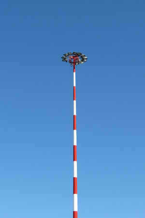 lamp post: Lamp post near an airport with alternate red and white painting