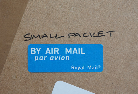 royal mail: LONDON, UK - CIRCA AUGUST, 2015: Small packet handwritten on a parcel - By air mail label by the Royal Mail