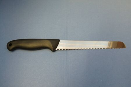 bread knife: Bread knife with black plastic handle over blue paperboard background