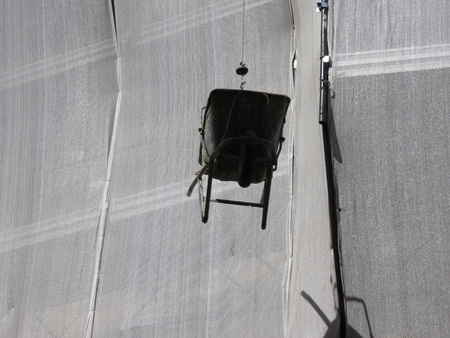 propelled: Wheelbarrow hand propelled vehicle in a building site suspended in the air