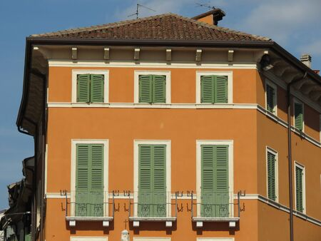 exterior architectural details: A traditional Italian house with colourful facade and green painted Venetian blinds, in Verona