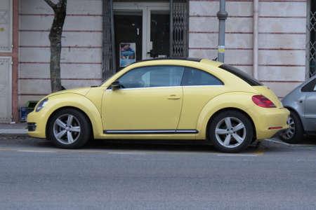 escarabajo: Cassino, Italia - alrededor de octubre de 2015: Amarillo Volkswagen New Beetle coche aparcado en una calle del centro de la ciudad Editorial