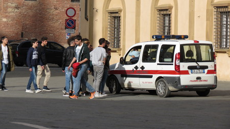 seizing: SIENA, ITALY - CIRCA APRIL 2016: Polizia muncipale (i.e. Town Police) seizing football ball of Italian schoolboys playing in the Cathedral square Editorial