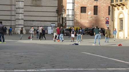 schoolboys: SIENA, ITALY - CIRCA APRIL 2016: Italian schoolboys and schoolgirls in a schooltrip playing foot in the Cathedral square Editorial