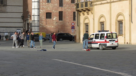 seizing: SIENA, ITALY - CIRCA APRIL 2016: Polizia muncipale (i.e. Town Police) seizing football ball of  Italian schoolboys playing in the Cathedral square