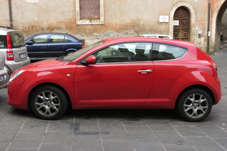 red centre: ROME, ITALY - CIRCA OCTOBER 2015: red Alfa Romeo Mito car in a square of the city centre.