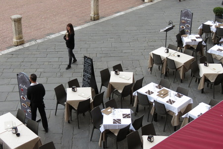 costumers: SIENA, ITALY - CIRCA APRIL 2016: unidentified waiters waiting for costumers at an outdoor terrazzo restaurant Editorial