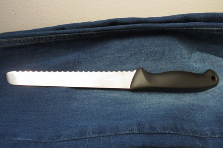 bread knife: Bread knife with black plastic handle over blue jeans fabric