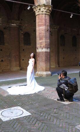 asian bride: SIENA, ITALY - CIRCA APRIL 2016: Asian bride posing for her photobook in an historical location Editorial