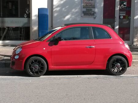 red centre: ROME, ITALY - CIRCA OCTOBER 2015: red FIAT 500 car (new version) parked in a street of the city centre