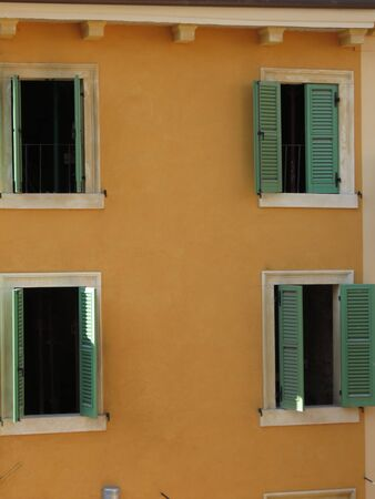 traditional house: A traditional Italian house with colourful facade and green painted Venetian blinds, in Verona