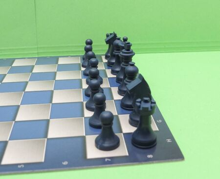 checkers: Wooden chessboard with black and white plastic checkers