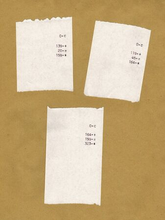 finger proof: Three bills or receipts isolated over light brown background