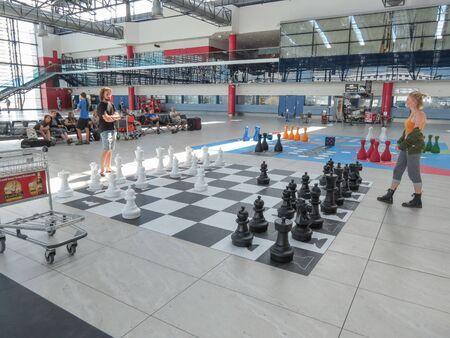 t short: PRAGUE, CZECH REPUBLIC - CIRCA JULY 2016: couple playing chess on a floor chessboard at Vaclav Havel international airport