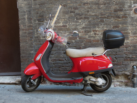 SIENA, ITALY - CIRCA JULY 2016: red Vespa motorcycle parked in a street of the city centre Editorial