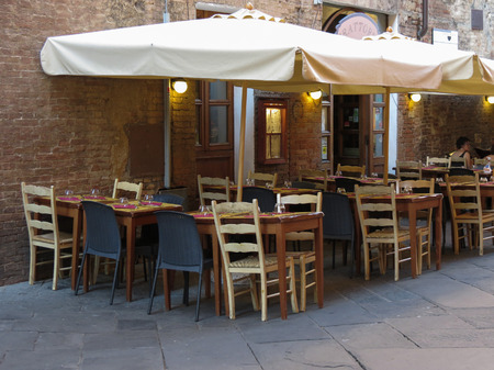 COSTUMERS: SIENA, ITALY - CIRCA JULY 2016: outdoor restaurant with tables and chairs Editorial