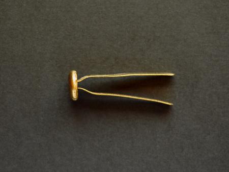 Brass fastener, brad, paper fastener or split pin over black background