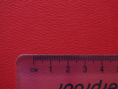 centimeters: plastic ruler over red paper background showing centimeters