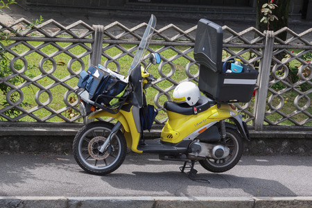 MILAN, ITALY - CIRCA JULY 2017: yellow Piaggio Liberty scooter used by a postman of Poste Italiane (meaning Italian Mail) to deliver mail