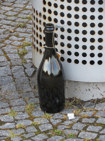 disposed: dark glass bottle of wine disposed of on the pavement Stock Photo
