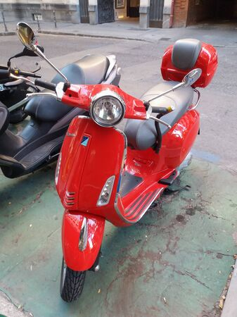 MADRID, SPAIN - CIRCA OCTOBER 2017: red Vespa motorcycle parked in a street of the city centre Editorial
