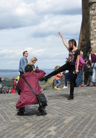 EDINBURGH, SCOTLAND, UK - CIRCA AUGUST 2015: Asian tourist posing for a picture in front of the Edinburgh castle