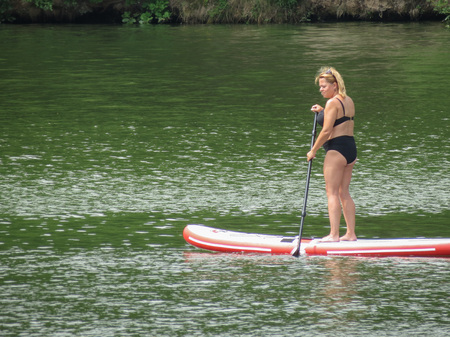 BRNO, CZECH REPUBLIC - CIRCA JUNE 2018: unidentified woman paddling on a sup surf on the lake