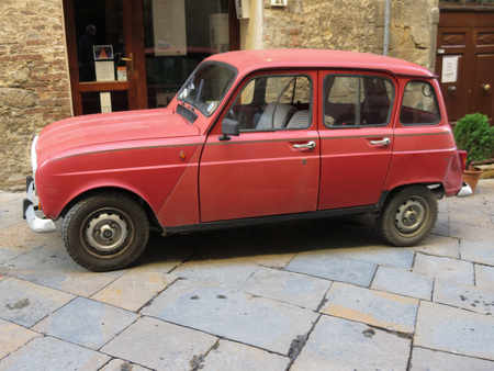 VOLTERRA, ITALY - CIRCA DECEMBER 2014: red Renault 4 car parked in a street of the medieval city centre