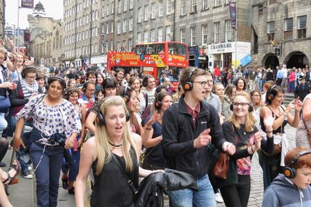 EDINBURGH, SCOTLAND, UK - CIRCA AUGUST 2015: crowd of people in a silent disco performance at the Fringe street festival on the Royal Mile, the main street of Edinburgh