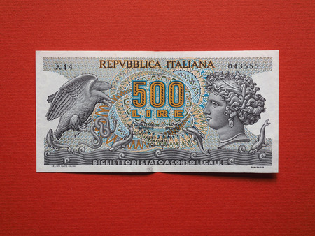 Vintage withdrawn Italian 500 Lire banknote over red background