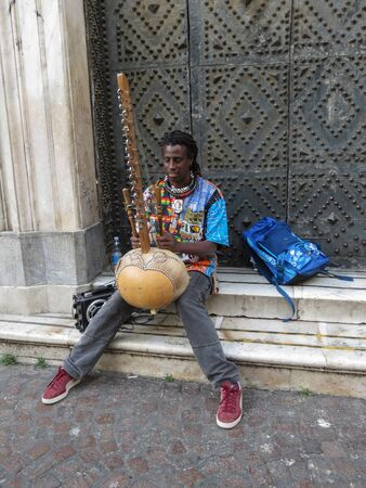 NAPLES, ITALY - CIRCA JUNE 2019: unidentified African harp kora player performing in the streets of the city centre