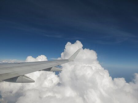 right wing of an aircraft flying over white clouds Stok Fotoğraf