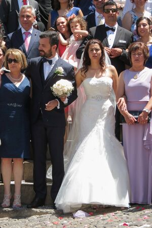 COIMBRA, PORTUGAL - CIRCA JUNE 2015: bride, groom and wedding guests in front of the church Se Velha de Coimbra (meaning the Old Seat or Old Cathedral in Coimbra)