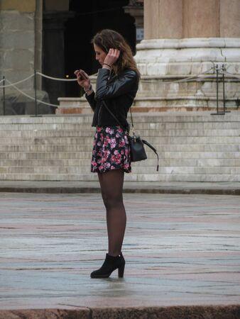 BOLOGNA, ITALY - CIRCA APRIL 2018: unidentified stylish woman with mobile phone Redakční