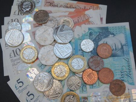 LONDON, UK - CIRCA DECEMBER 2019: Pound banknotes and coins (GBP), currency of United Kingdom