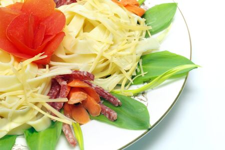 Pasta with cheese, salami, tomatoes and herbs on a white plate, isolated photo