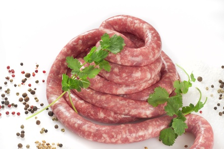 a natural raw sausage on white with spices and herbs Stock Photo