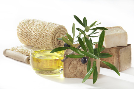 a still life on white of bath soaps with olive oil an twig Stock Photo