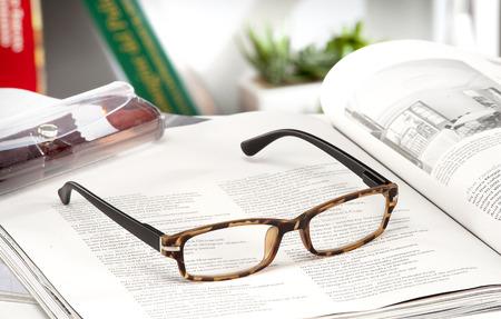 gafas de lectura: modernas gafas de lectura anotadas en una revista en casa Foto de archivo