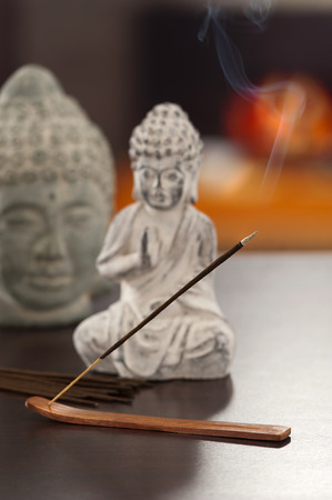 buddah: an incense on the table at home smocking with a out of focus fireplace